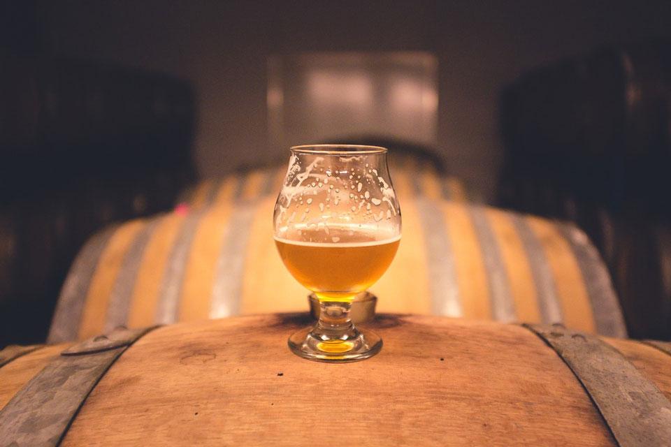 Ein Bierglas steht im Bierkeller auf einem Holzfass