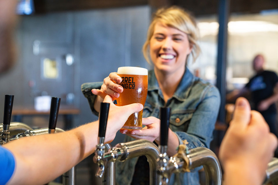 Eine Biertrinkerin bekommt ein frisch gezapftes Bier gereicht