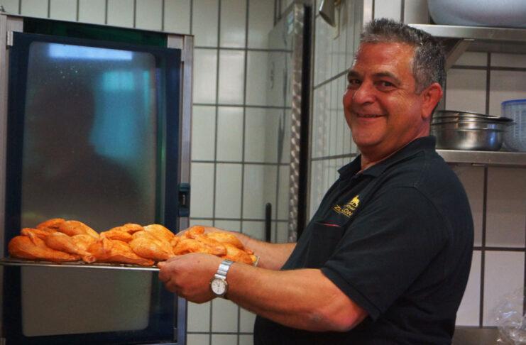 Wirt Seppi Spiess schiebt Poulets in den Ofen die für den Abholservice zubereitet werden